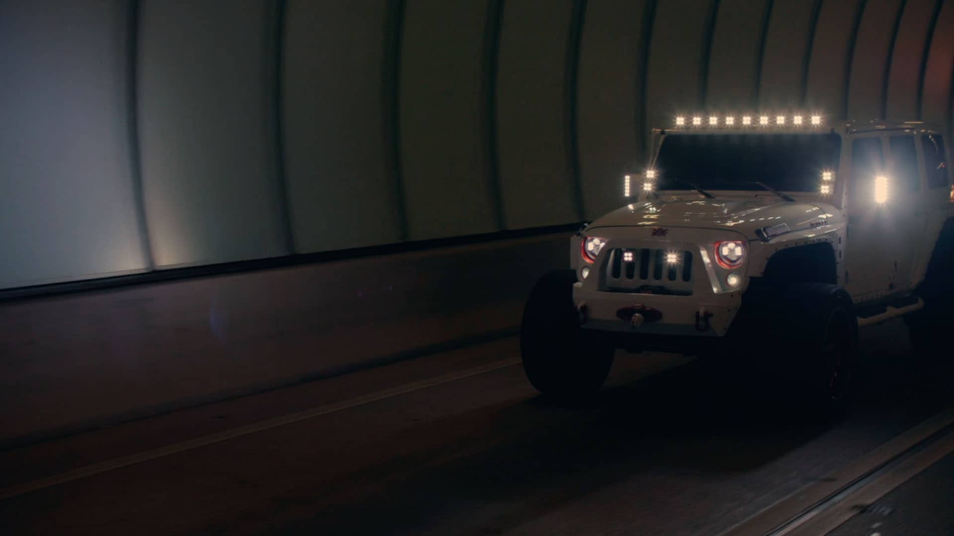 A white, tuned-up Jeep with lights on crosses a dark tunnel