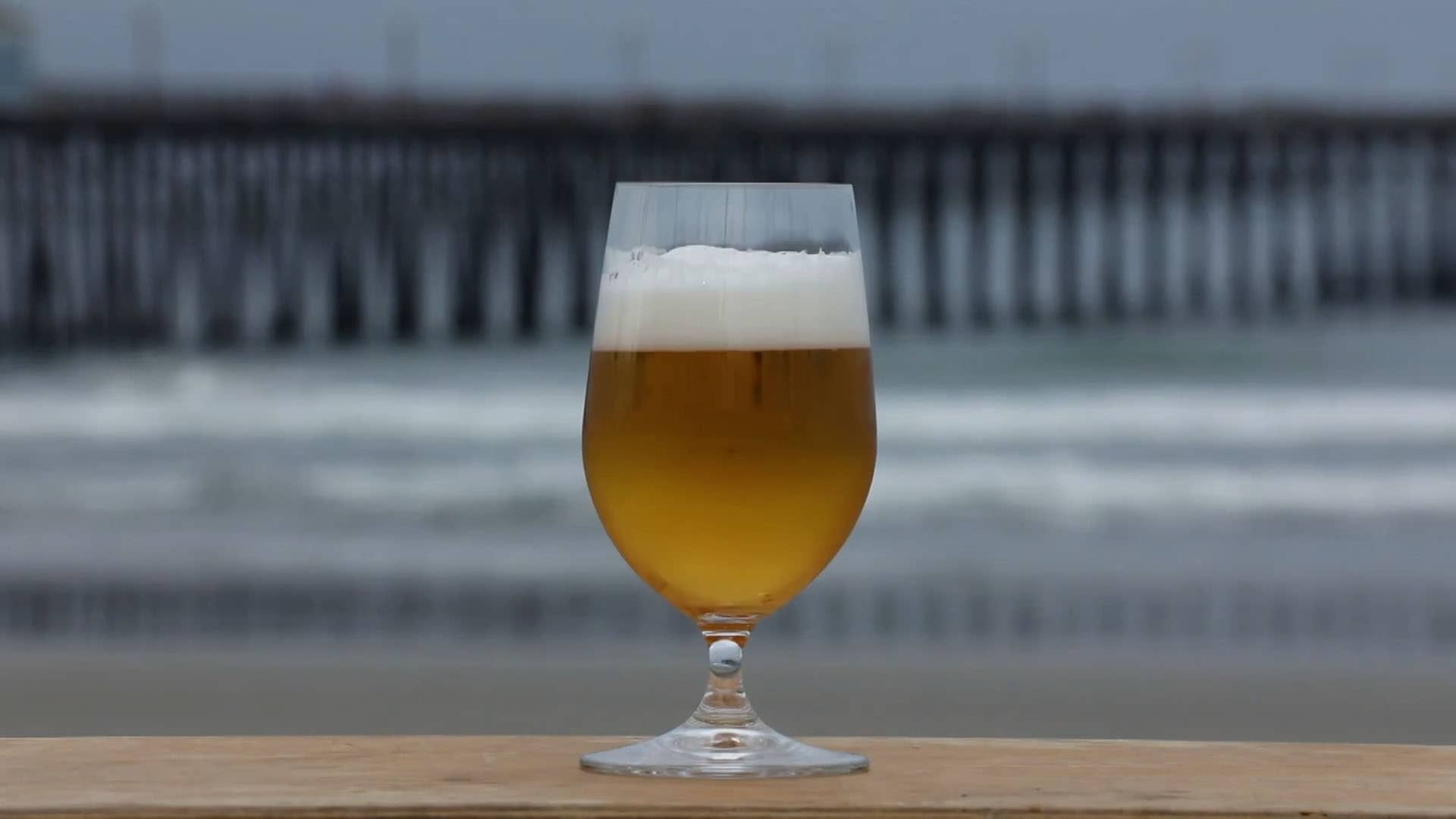 A glass of beer over a wooden countertop, with a beach and a long pier as background