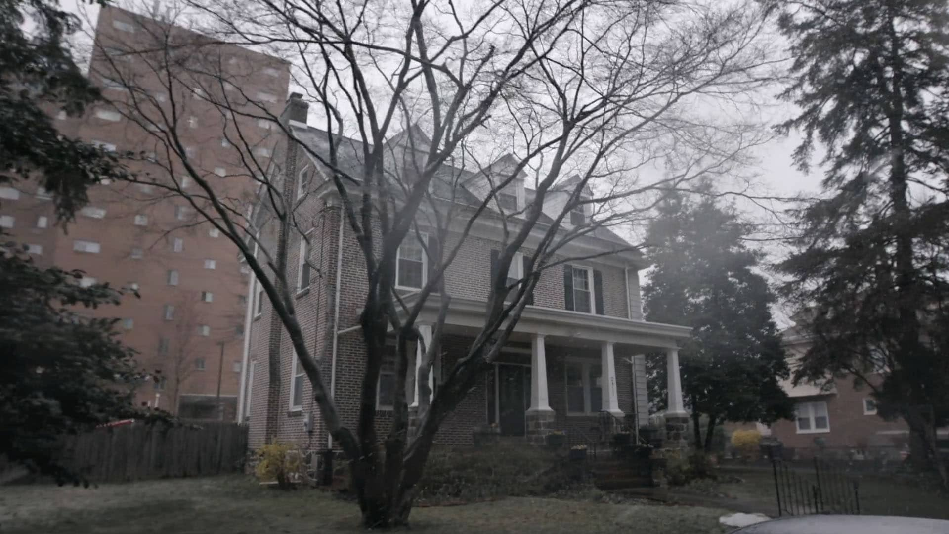 Foggy view of a two-story house, with overcast skies