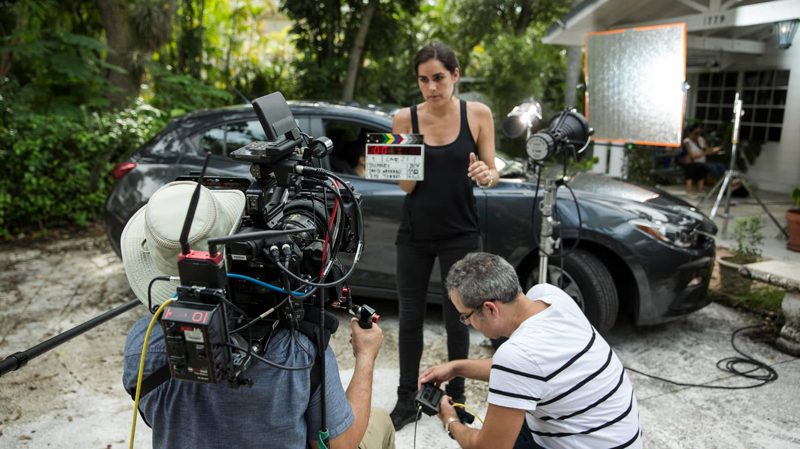 Woman holds clapperboard in front of cameraman and director David Navarro