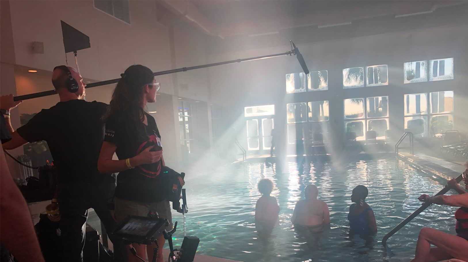 A production crew works around a swimming pool with a group of elder swimmers