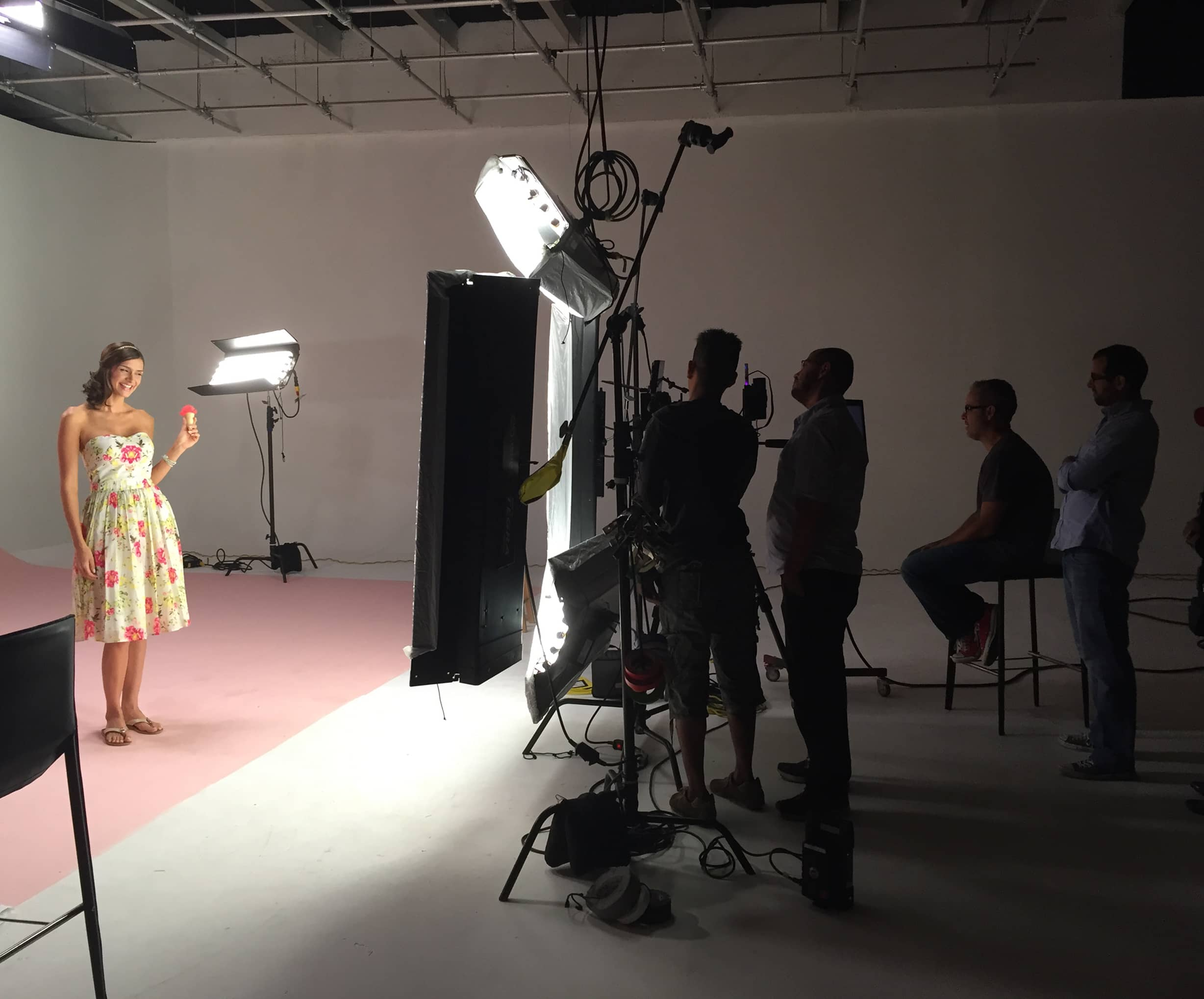 Young girl wearing floral dress and crew members in studio video shooting session